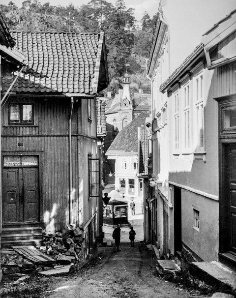 Grandbakken: Dette bildet er trolig tatt en gang på 1930-tallet. Bakken har fått navnet etter Grand Hotell, som holdt til i det bygget til høyre, som nå blir kalt for «Blåkorsgården». Til venstre er Isaksens hus. Her holdt frisør Halvorsen til i mange år. Til høyre en liten bolig som ble revet for at Blåkors skulle få ny inngang, noe som aldri skjedde. Der det lille trehuset sto er det parkering. Nede på Torvet kan man se den gamle Narvesen-kiosken og der Skagerrak Sparebank holder til, står ennå det spesielle tårnet.