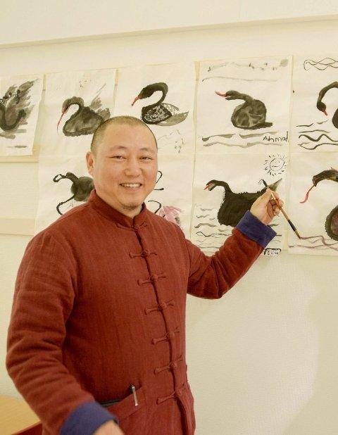 GJENSYN MED BERLEVÅG: Den kinesiske filmskaperen Steven Gao kommer til Berlevåg med en rekke kort- og langfilmer. Da han var i Berlevåg sist, hadde han malekurs med elevene på skolen. Her viser han fram elevenes kunstverk.