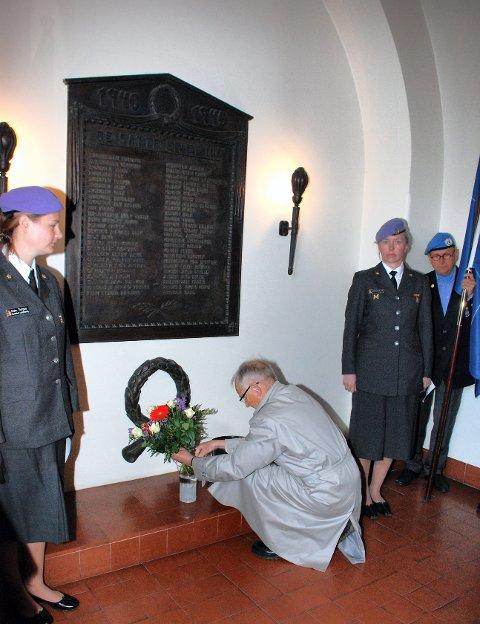 Her ser vi en tidligere kransenedleggelse fra 8. mai 2010, i våpenhuset i Sandefjord kirke, foran minnetavelene over falne i 2. verdenskrig. Thorvald Trogstad fra Sandefjord Forsvarsforening satte på plass bukettene.