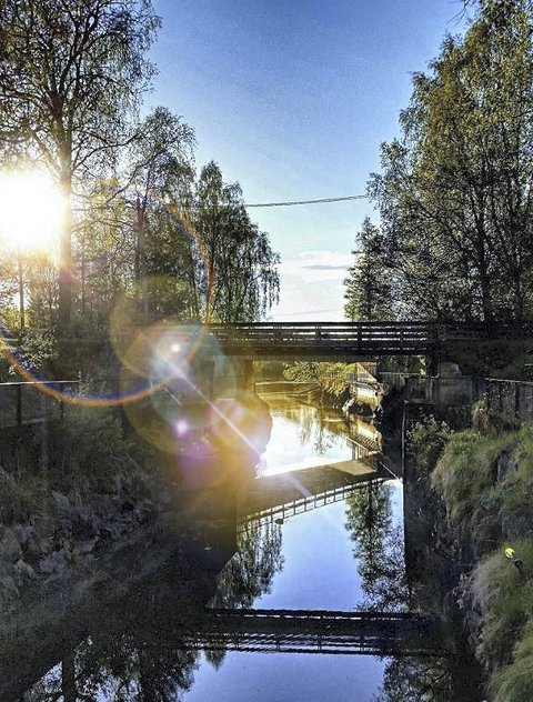 Vinner uke 24: Et fint fotomotiv der jeg synes solrefleksjonen i linsa gjør bildet mer spennende. Linjene fra bruene som speiler seg i slusa gir en god komposisjon. Foto: karina Kvernes