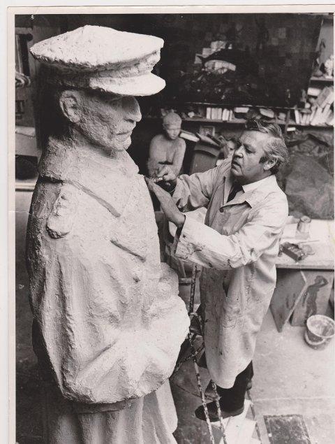Verker av Ørnulf Bast stilles ut i Soldathjemmet lørdag og søndag. Med dem utstilles bilder av arbeidet hans. Her er Bast mens han modellerer Haakon 7.-monumentet.