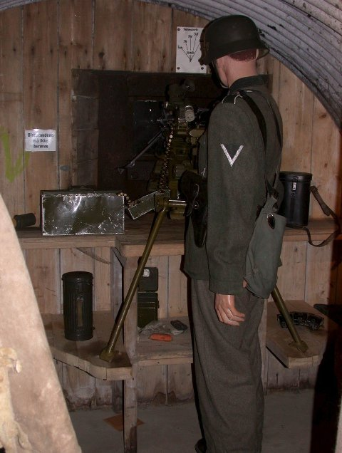 Hovedrommet i bunkeren. Fra denne plasseringen med skyteskår har man god utsikt til Sarpsbrua, våpenet er en MG-42. Ved siden av hovedrommet er det innredet et sambands- og hvilerom. (Foto: Mona Beate Vattekar/Østfoldmuseene)
