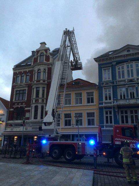 Klokekn 0504 velter det fortsatt røyk ut av bygget. Brannvesenet slukker med kranbiler på to sider av husrekken.FOTO: GEIR JETMUNSEN