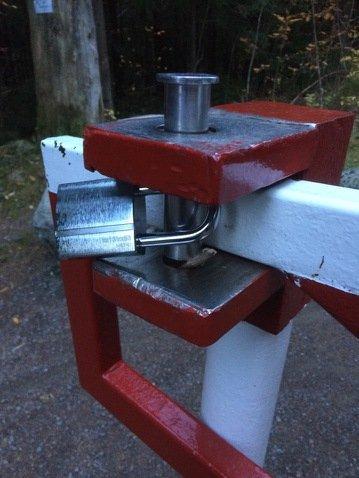 BER OM TIPS: Noen hadde blokkert nøkkelhullet til denne hengelåsen, som henger på bommen på Sørskogveien. Familien Sørskogen ber folk tipse politiet dersom de har sett hvem som står bak hærverket.