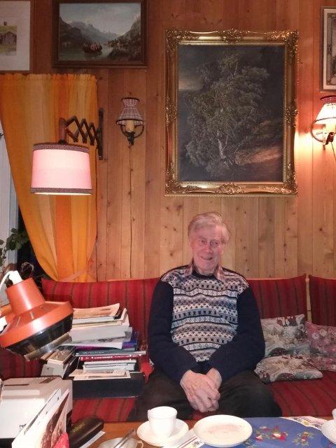 FORFATTEREN: Alltid noe å arbeide med lett tilgjengelig i sofaen. Maleriet rett bak forfatteren er gave fra Alvdal Kommune.