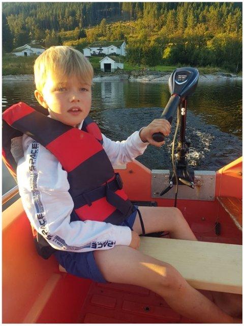 Båttur: Barnebarnet vårt, Lian Bugge Tjugum, styrer båt med elektrisk motor på Hafstadvatnet ved Meisingset. I bakgrunnen ser dere også hytta vår  Foto: Odd Jostein Løseth