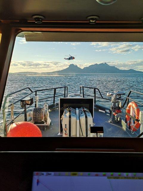 Sea Kingen heiser opp de tre ungdommene som ligger på båtens kjøl.