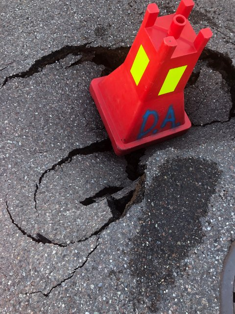 DYPERE: Bukken står oppå asfalten som har gitt etter når underlaget er blitt skylt unna. Under asfalten er hullet enda dypere enn dette.