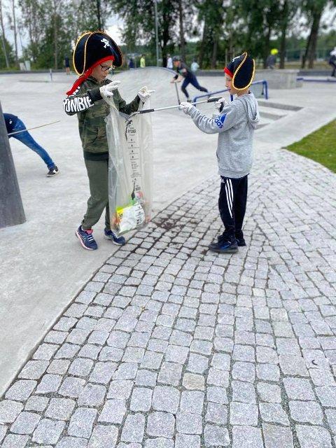 HJELPER HVERANDRE: Tobias Høyem Heiestad hjelper Emil Fagernæs Tråstadkjølen å plukke søppel.