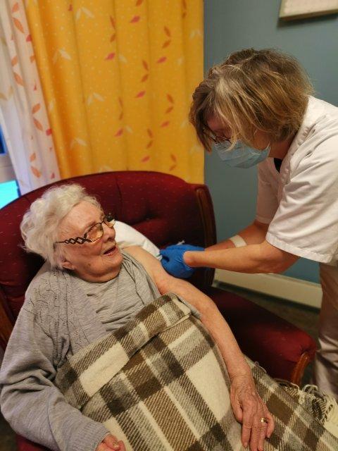 FØRSTE STIKK: Anfrid Mimmi Hethey tok første stikk i Eidskog. Fagansvarlig sykepleier Marlene Robertsson  ved Eidskog helsetun sørget for at 102-åringen fikk den første vaksinedosen mot koronaviruset. FOTO: MALIN ØDEGÅRD
