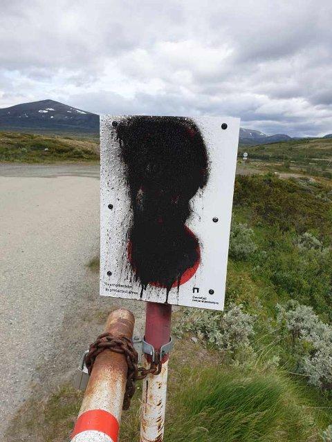 Skiltet ved bommen på Snøheimvegen i Dovrefjell er tagget ned.