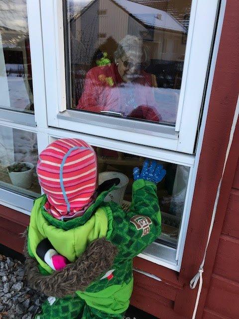 Innanfor vindauge sit Grethe Sollesnes.