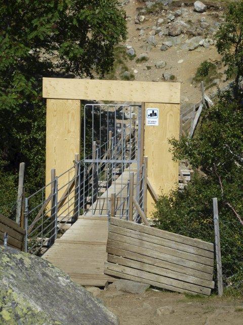 STENGT: Denne stien over brua inst i Valldalen er stengt for alle, med unntak av sau og sauegjetarar. Portalen og stålporten har vekt oppsikt blant fotturistar. Foto: Sigmund Hansen