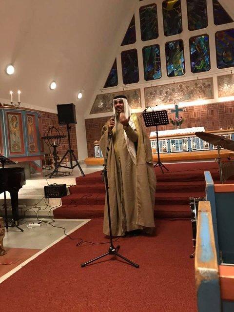 BIDET: Dette er bildet som ble delt av Abdullah Bin Zidan (45) kledd i sin irakiske nasjonaldrakt i Hammerfest kirke. Her leser han to dikt om kjærlighet og flukt.