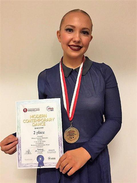 Louise Quist Nordvold fra Lierfoss med sølvmedaljen hun nylig var med å sikre Norge under formasjonsdans i VM for jazz/moderne dans i Polen. Foto: Privat