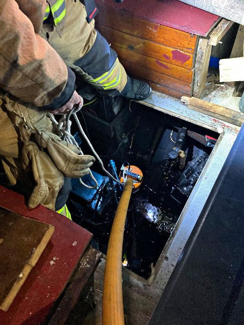 HJALP TIL: Brannmester Thomas Nordby hjalp en båteier i Holmestrand med å pumpe ut vann fra båten. Brannvesenet satte igjen sin pumpe over natten, slik at båteier kan få skaffet seg en ny i dag.