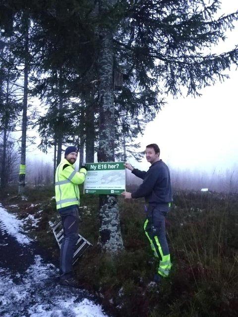 I TRASÉ C: Marius Holm Enerud (t.v.) og grunneier Hans Espen Lodding viser fram plakaten som skal advare mot den mulige motorveiutbyggingen i Ullensaker.