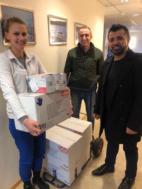 FIKK HANSKER OG PIZZA: Sif Petursdottir i Lillestrøm kommune (t.v.) fikk engangshansker av Samad Rah. Ahmed Al-Jaf spanderte pizzalunsj på alle de ansatte.