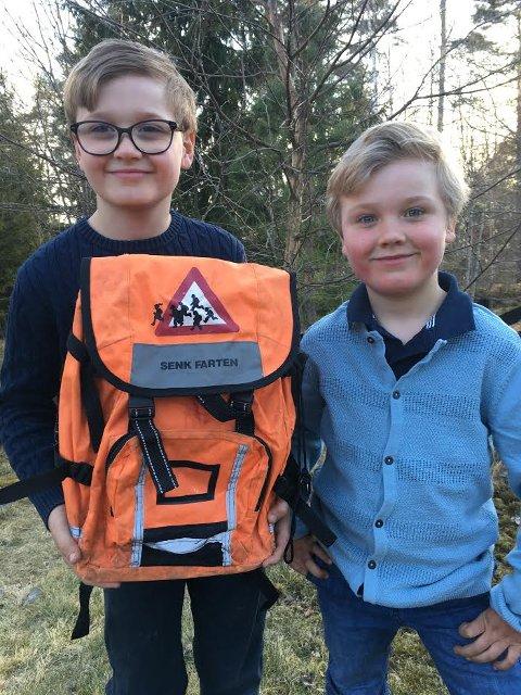 SKOLESEKK: Storebror Markus (10) fikk en slik oransje skolesekk da han begynte i 1. klasse. Det vil gjerne også lillebror Oskar (6) ha. Nå vil politikerne i Våler vurdere om ordningen med gratis skolesekker skal videreføres der.