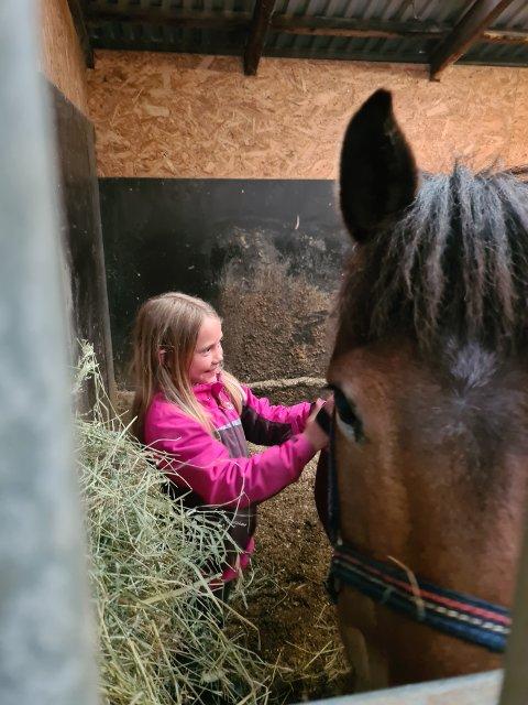 HOBBY: Otilje Hammer (8) er tydelig glad for at hun skal ha ridetime. Hun forteller at dette er det beste hun vet å holde på med og skulle gjerne sett at mamma og pappa lot henne ha hest heime på Kolvereid.