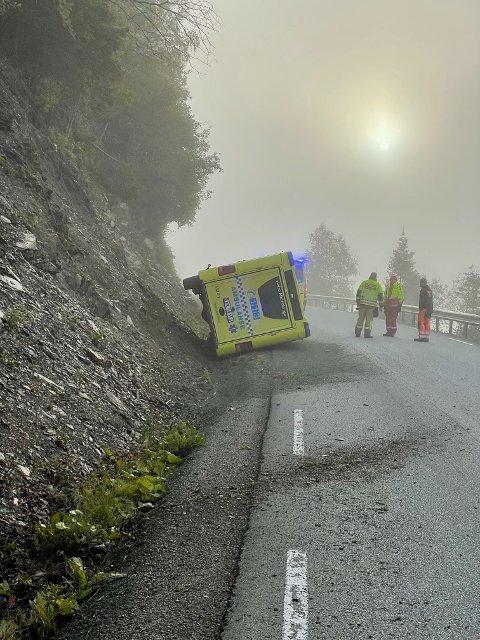 PÅ SIDEN: Her ligger ambulansen på siden. Til slutt kom personene i bilen seg ut på egenhånd.
