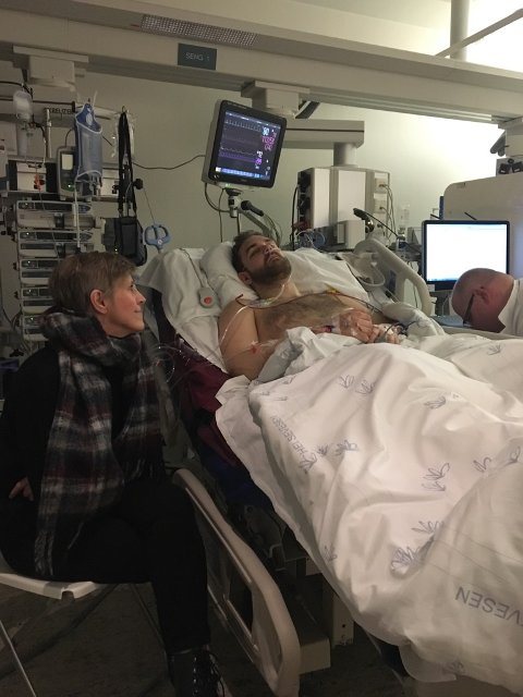 ALVORLIGE BRUDDSKADER: Her ligger Bendik Liland Pedersen (27) på sykehuset med alvorlige bruddskader. Ved siden av sitter moren.