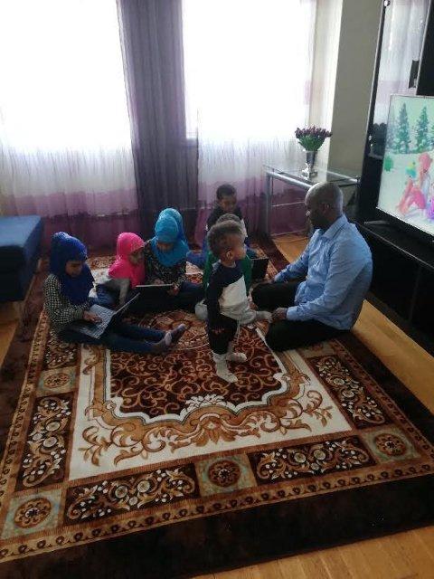 SAMLING: Litt lek og litt lekser. Skolen hjemme hos seksbarnsfamilien krever mye av foreldre og barn. Pappa Mohammed tar seg av barna slik at mamma Muna skal få tid til sin egen skoledag.
