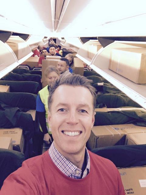 Laster flyet: Lasse Sandaker-Nielsen i flyet som lastes med skoleutstyr og nødhjelp.