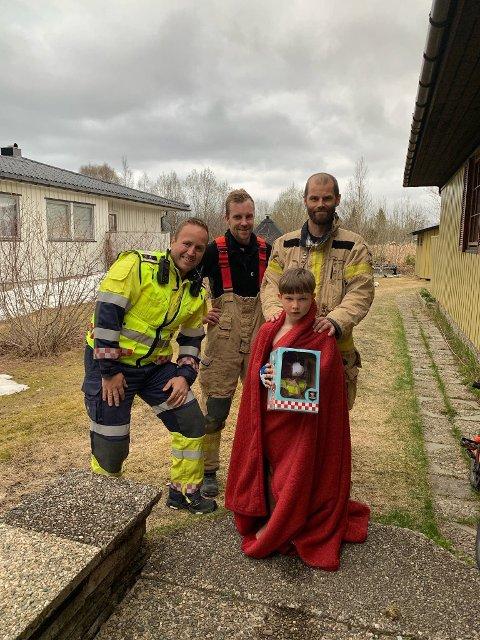 Isak (8) sammen med brannmannskapene som hyller han for å reagere lynraskt.