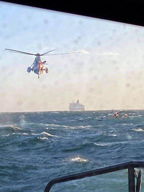 DRAMATISK: Slepeoppdraget utviklet seg til å bli et redningsoppdrag i fem-seks meter høye bølger. Her blir de to havaristene heist om bord i 330-skvadronens redningshelikopter.