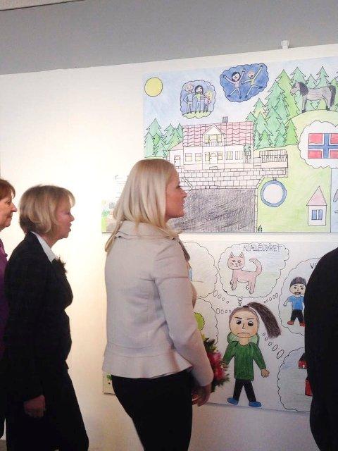 SER PÅ AURORAS TEGNING: Kronprinsesse Mette-Marit tok seg tid til å kikke nærmere på utstillingen som åpnet tirsdag. Øverst henger tegningen til Båstad-jenta Aurora Novak Orderud.