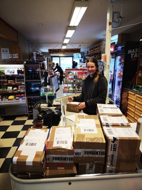 PAKKAR: Det hopar seg opp med pakkar på butikken i Undredal. Lise Berntsen er i full sving.
