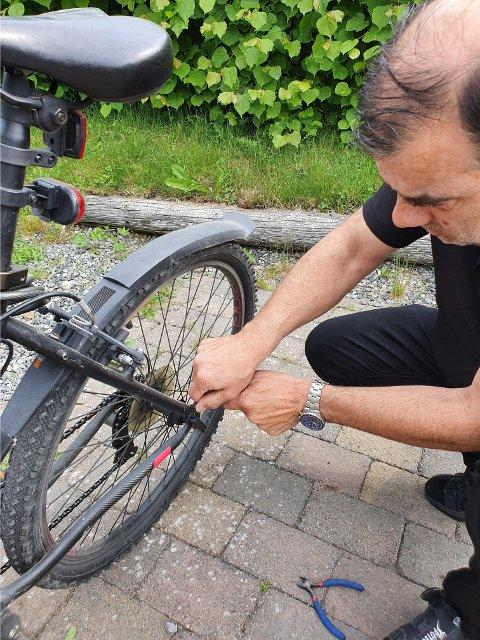 DEMONSTRER: Lars Terje Tveitan fester en strips på låsehendelen til bakhjulet på sønnens sykkel.