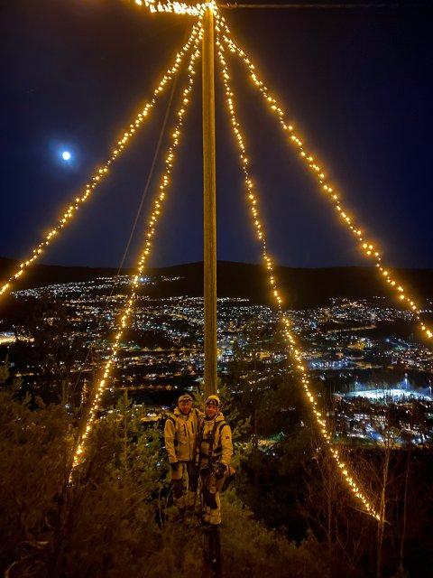 LYSER OPP: Egil Haugan og Fredrik Vander satte opp julelysene på Vindsås fredag kveld. De kan ses fra store deler av byen.