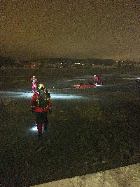 MÅTTE SVØMME: For å komme helt bort til båten måtte brannmannskapene svømme i råka. Personen i båten fikk også tørrdrakt og iførte seg denne.