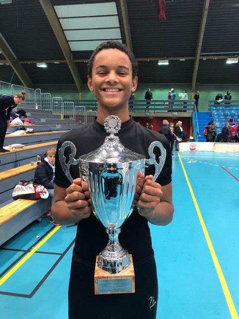 STOLT: Lukas Tadjo Takotue viser stolt fram vandrepokalen Nøtterøy-troppen vant for beste sammenlagte poengsum i tumbling og trampett i Drammen sist helg.