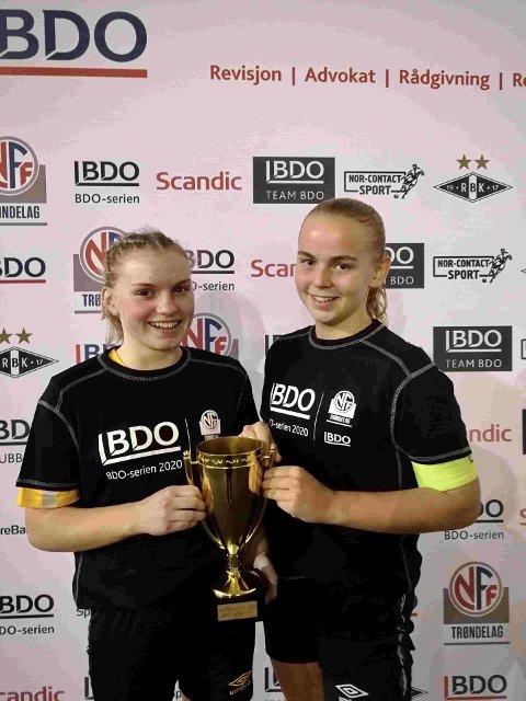 GA MERSMAK: Hermine Duclos Brønlund og Nila Nerli Hatling med det tydelige bevise på at SFK J17 er vinner av kretsmesterskapet i fotball 2020.