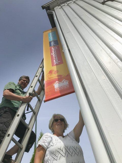 Noen stikker av med næringsforeningens bannere. Nå er to stykker stjålet. Bildet viser Solveig og Jarmo Røvik som hang opp bannerne i fjor sommer.