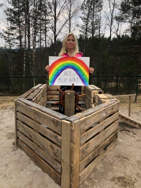Anette Gjermones med oppmuntrende melding til barna i Dølemo barnehage. Båten hun står i har de ansatte laget nå i disse korona-tider.