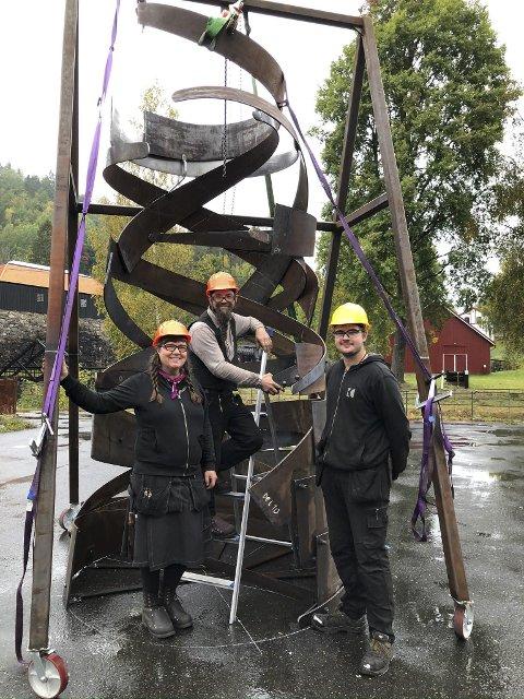 Nytt og gammelt: Øverst på skulpturen er det en rustfri plate som symboliserer overgangen til moderne industri. (f.V) Monica, Benjamin og lærlingen Ask Martens. Foto: Siri Fossing