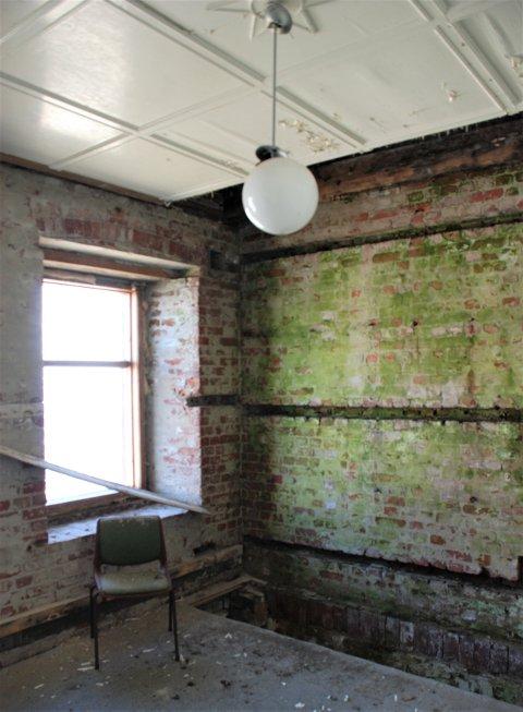 Store fuktproblemer har ført til at all innvendig foring er fjernet og et stort hull er skåret ut i dekkene for å lufte mellom etasjene og stoppe fukten. Bildet viser fyrbygningen, vegg mot sørøst.