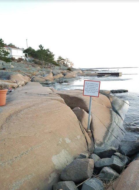 Skiltet med teksten «Du er velkommen til å passere over vår eiendom, men respekter at opphold og bading ikke er tillatt» står helt nede ved sjøen. Et par meter innenfor er en keramikk-krukke plassert. Hytta i bakgrunnen har ikke nødvendigvis noe med skiltet å gjøre.