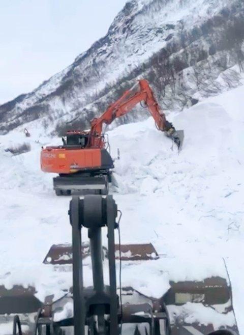 STOR RYDDEJOBB: Børre Andersen AS er igang med å fjerne skredet som gikk over fylkesveien i Skillefjord. De må bruke gravemaskiner for å rive løs snøen etter gigantskredet.