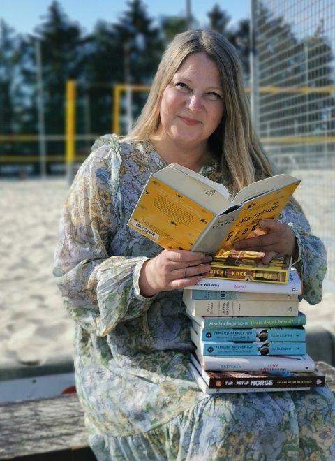 Det er kanskje ferie, men biblioteksjefen tar gjerne med seg litt ekstra lesestoff.