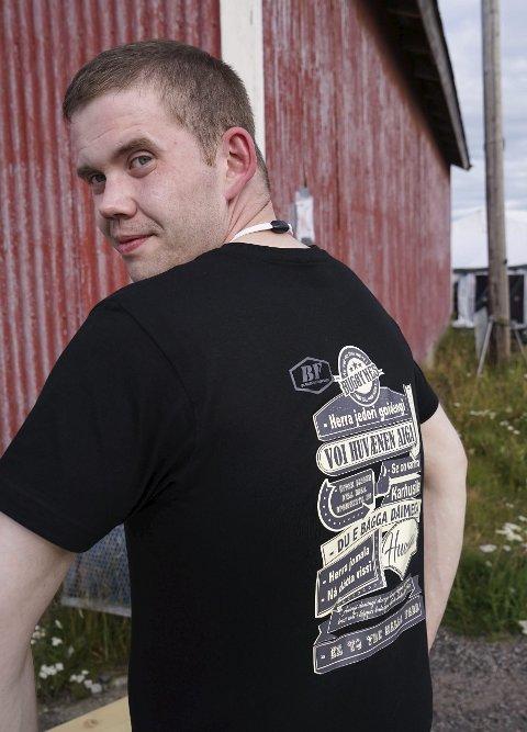 BRA SALG: Arnt Ove Bueng viser fram den splitter nye Bugøynes-skjorta med finske uttrykk skrevet med norske bokstaver. Lørdag solgte han mange av dem fra standen på Bugøynesfestivalen.