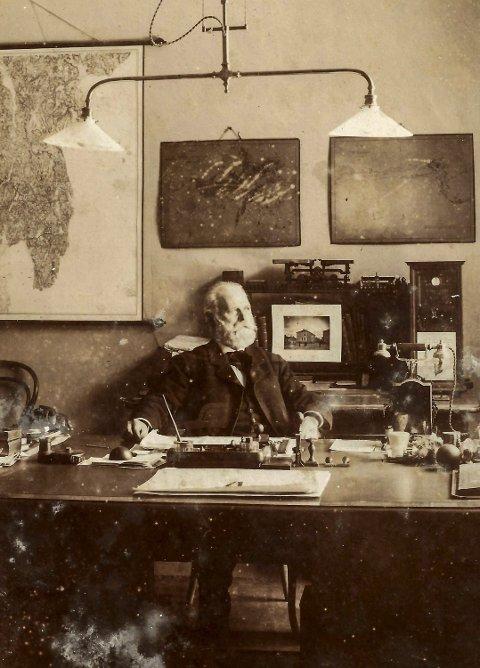 STADSINGENIØREN: Gustav Blom Kielland fotografert på sitt kontor en gang etter år 1900, det året da Kielland sørget for at det kom elektrisitet til Halden. I bakgrunnen skimtes kart over byen og et bilde av Haldens nye rådhus på Wiels plass. KIELLANDS FOTOARKIV