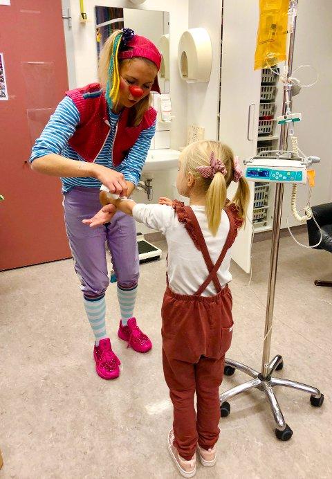 PETRINE-PLASTER: – Det er gøy å ha noen å leke med når jeg er på sykehuset, ellers er det ganske kjedelig. Det er morsomt når vi leker gjemsel. Noen ganger skriver de klovnkort til meg og jeg har samlet 28 sånne med bilder av sykehusklovnene på, forteller Elly. Her får hun plasterassistanse av klovnen Petrine. FOTO: Privat