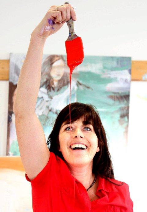 FARGER: Kunstner Kristin Romberg er livsglad og fargerik. Her vil jeg  få fram ansiktet samtidig som hun viser hva hun driver med. Legg merke til komposisjonen med rød maling og rød genser. I tillegg plasserer jeg malingstrålen gjennom øyet hennes. Og jeg rammer inn Romberg i hennes eget maleri i bakgrunnen