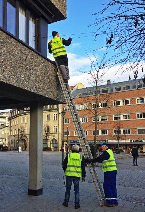 Ingebrigt Rygg, Jan Erik Grønvold og Dagfinn Erlandsen strekker lyslenken mellom Interoptik og Sparebank1 Ringerike Hadeland ved Søndre torg.