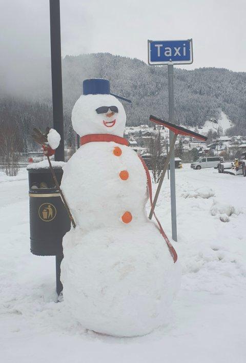 Smiler bredt: Snømannen smiler bredt der han står ved taxiholdeplassen i Bagn.